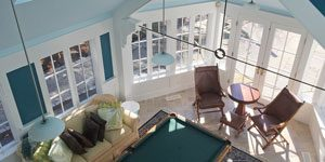 Looking down from stairway onto pool table and French doors